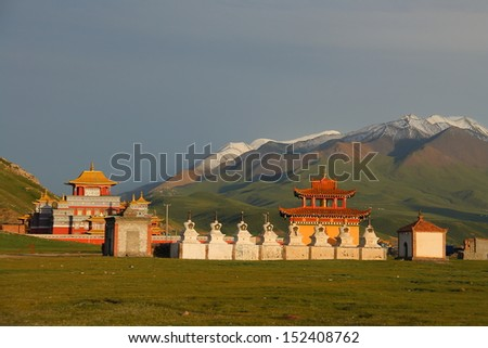 Grand and gorgeous new Gerisi Temple on Tibetan Plateau, with snow mountains on the background, Qinghai, China - stock photo
