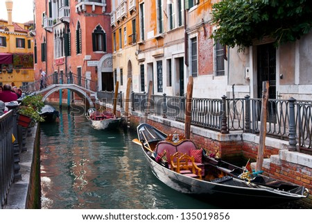 grand Canal in Venice, buildings bridge and gondola boat in stream of water. Venezia a city in Italy small islands separated by canals and linked by bridges. city and lagoon is World Heritage Site. - stock photo