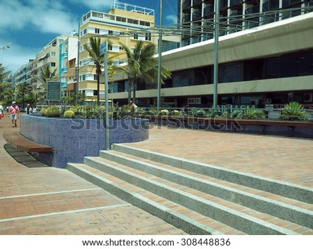GRAND CANARY ISLAND-MAY 9: A cactus garden is seen with tourists walking on pedestrian promenade Playa las Canteras in Las Palmas, Grand Canary Island, Spain on May 9th, 2015.   - stock photo