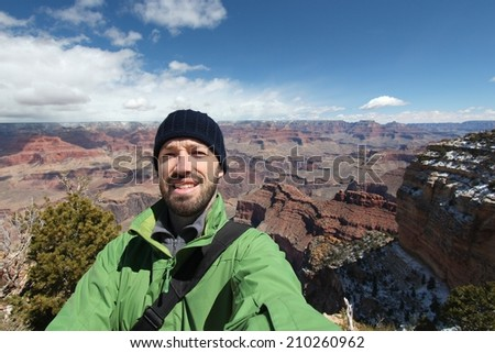 Grand Canyon National Park in Arizona, United States. Tourist taking a selfie photo during a hike. Young adult male traveler. - stock photo