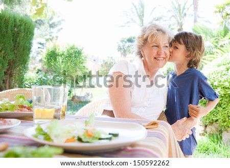 Grand child boy kissing grandmother on the cheek while having lunch together in a garden porch at home during a summer sunny day on vacation. - stock photo