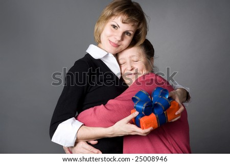grand daughter and  grandmother embrace each other with love - stock photo
