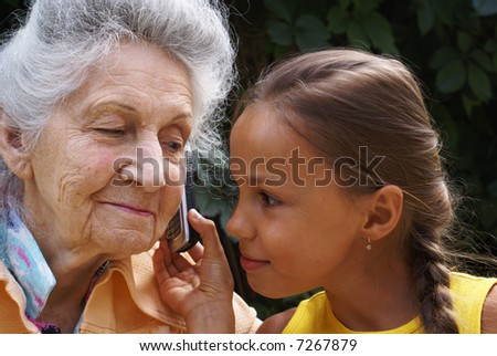 Grand daughter and her grand mother talk on mobile phone
