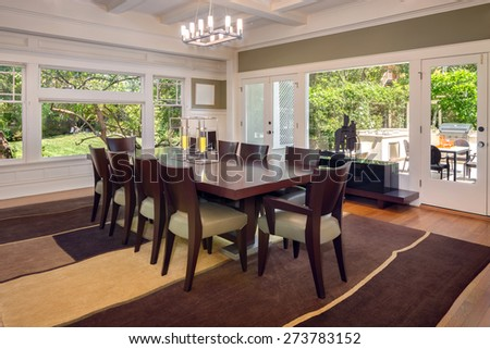 Grand Dining Room in Luxury Home with leaded glass view windows wooden floor and modern chandelier. - stock photo