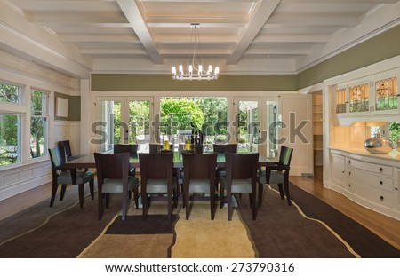 Grand Dining Room in Luxury Home with white wooden beams, leaded glass view windows wooden floor with rug, build ins and modern chandelier. - stock photo