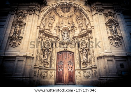 Grand doors of Saint Mary Basilica in San Sebastian (Donostia), Spain. Entrance in high arch with a lot of sculpture in it and statues on walls. View in dark shadowed frame. Architecture of Europe. - stock photo