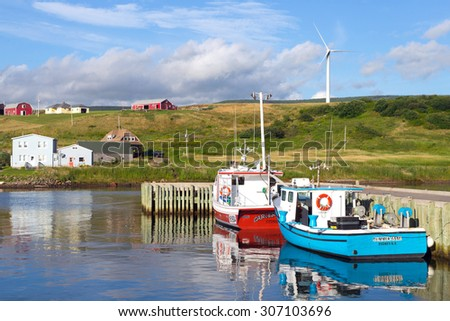GRAND ETANG, CANADA - AUGUST 6, 2015:  Picturesque rural scene with water and windmill on hillside, in Grand Etang on the famous Cabot Trail in Cape Breton, Nova Scotia - stock photo
