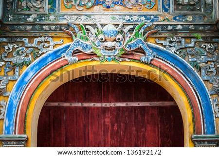 Grand gate in dark wood and colorful decoration with traditional symbol, Hue City in Vietnam. Imperial arch entry decorated with big dragon over doors and dragon pattern around. Architecture of Asia. - stock photo