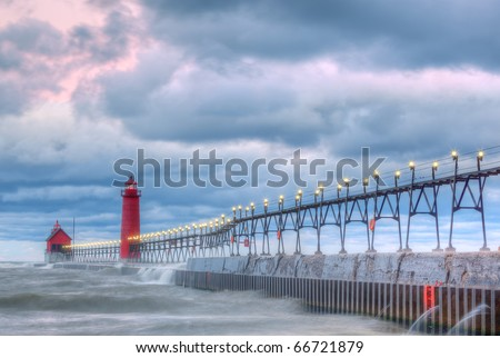 Grand Haven, Michigan Lighthouse at dawn with surf flowing over pier, Lake Michigan, USA