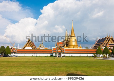 Grand Palace and Temple of Emerald Buddha complex in Bangkok, Thailand against blue sky.