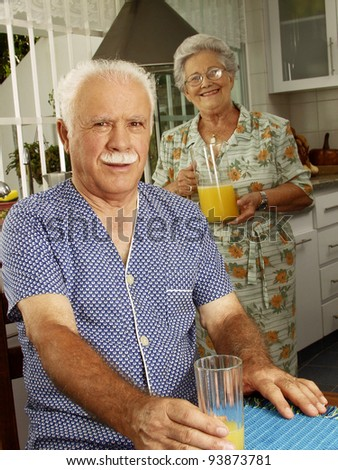 Grand parents drinking and pouring orange juice at kitchen. - stock photo