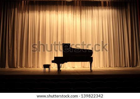 Grand piano at concert stage with brown curtain - stock photo