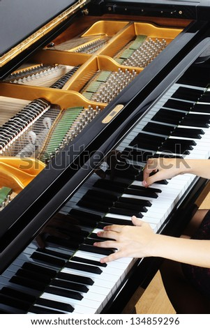Grand piano keys with hands on the keyboard. Pianist and musical instrument closeup - stock photo