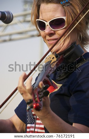 GRAND PRAIRIE, TEXAS - APRIL 15: An unidentified woman plays an electric violin on stage during the Lone Star Tea Party at QuikTrip Park on April 15, 2011 in Grand Prairie, Texas. - stock photo