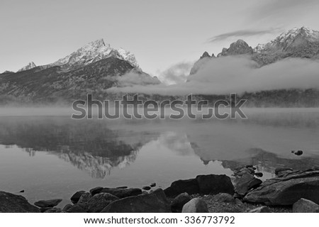 Grand Teton and the Teton range reflecting in lake with clouds clearing - stock photo