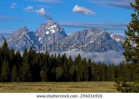 Grand Teton Mountain with glaciers and fog from the Snake River - stock photo