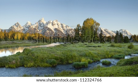 Grand Tetons range in morning light with river in foreground - stock photo