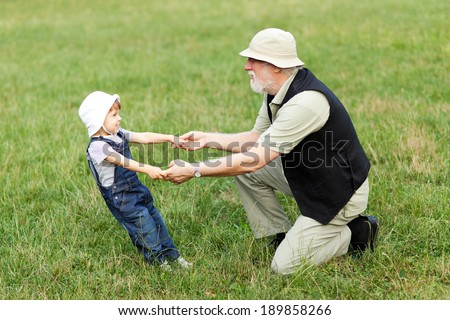 Grandchild and grandfather holding hands and having fun outdoor - stock photo