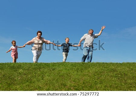 grandchildren and their grandparents running on hill and holding for hands