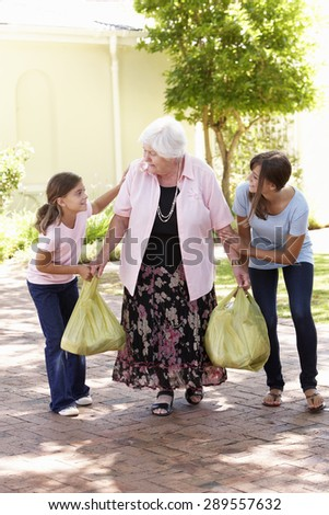 Grandchildren Helping Grandmother To Carry Shopping - stock photo