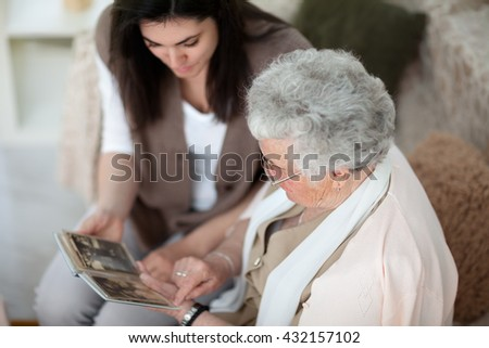 Granddaughter and grandma looking at old family album - stock photo