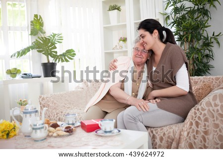 Granddaughter and grandma sitting on sofa and hugging - stock photo
