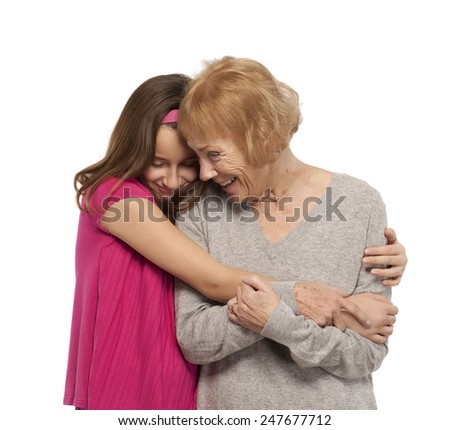 Granddaughter and grandmother embracing against white background - stock photo