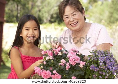 Granddaughter And Grandmother Gardening Together - stock photo