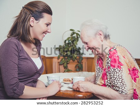 Granddaughter and grandmother laughing outloud - stock photo