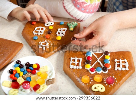 Granddaughter and Grandmother Making the Roof of Christmas Gingerbread House  - stock photo