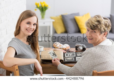 Granddaughter and grandmother smiling at a camera, watching old photographs in a warm, modern interior