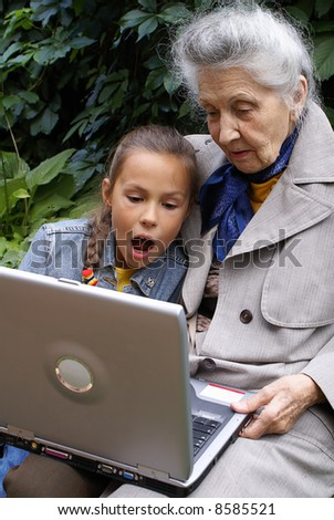 granddaughter and her grandmother are working on notebook computer - stock photo