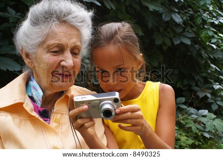 Granddaughter and her grandmother review digital camera pictures - stock photo