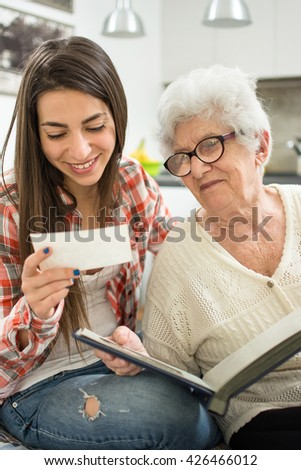 Granddaughter and her grandmother sitting on couch and ad looking at old photos. - stock photo