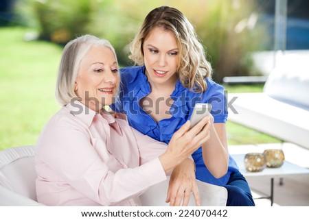 Granddaughter assisting senior woman in using smartphone at nursing home porch - stock photo