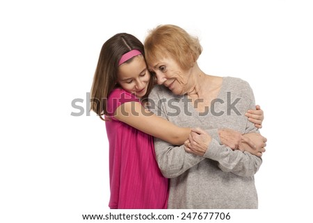 Granddaughter embracing her grandmother against white background - stock photo