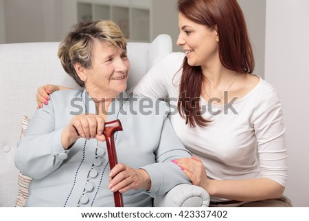 Granddaughter embracing her old and disabled grandma, senior lady holding walking stick - stock photo