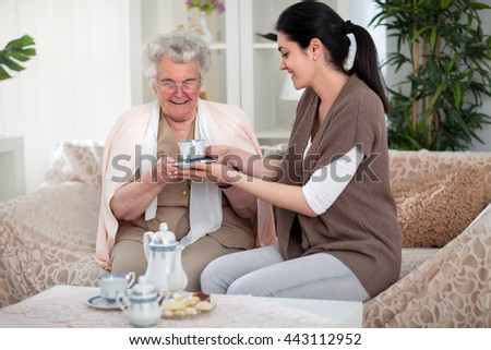 Granddaughter giving a cup of tea to her grandma - stock photo