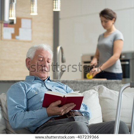 Granddaughter helping disabled grandpa in domestic duties - stock photo