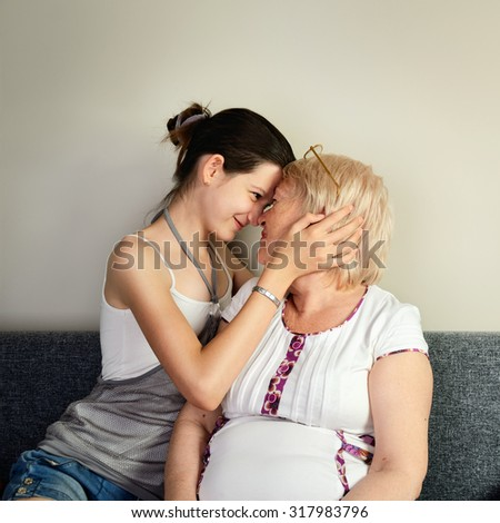 granddaughter hugging her grandmother and pressed against her face square format - stock photo