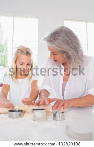 Granddaughter making biscuits with her grandmother in the kitchen