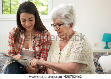 Granddaughter solving crosswords puzzle with the help of her grandmother at home. - stock photo