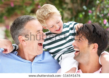 Grandfather And Father Giving Grandson Ride On Shoulders - stock photo