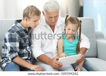 Grandfather and grandchildren with tablet on couch