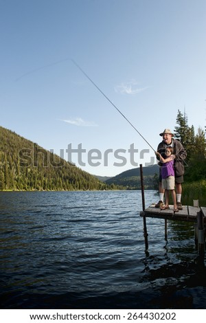 Grandfather and Granddaughter Fishing Together - stock photo