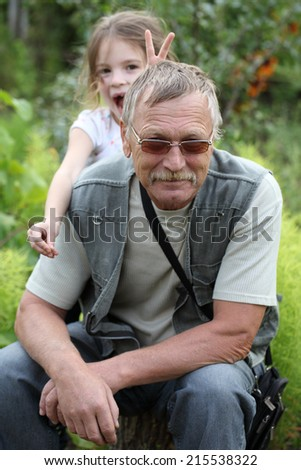 Grandfather and granddaughter girl playing in the garden. Outdoors active lifestyle. - stock photo