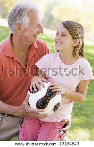 Grandfather and granddaughter outdoors with ball smiling - stock photo