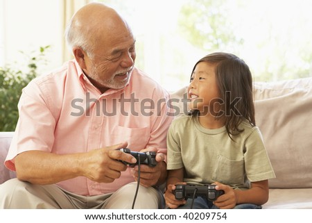 Grandfather And Granddaughter Playing Computer Game At Home - stock photo