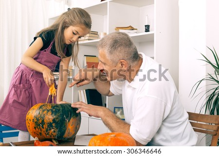 Grandfather and granddaughter playing with pumpkin on Halloween night. Selective focus and small depth of field. - stock photo