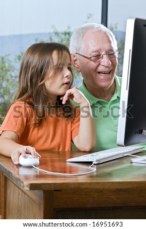 grandfather and granddaughter with computer at home